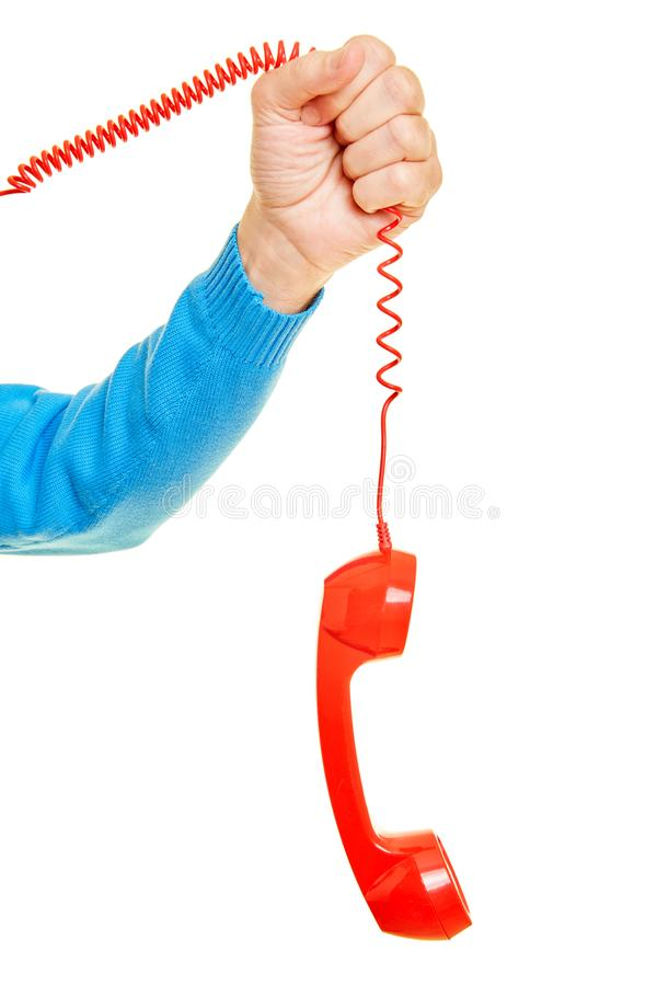 Hand is holding red telephone receiver on cable royalty free stock photography