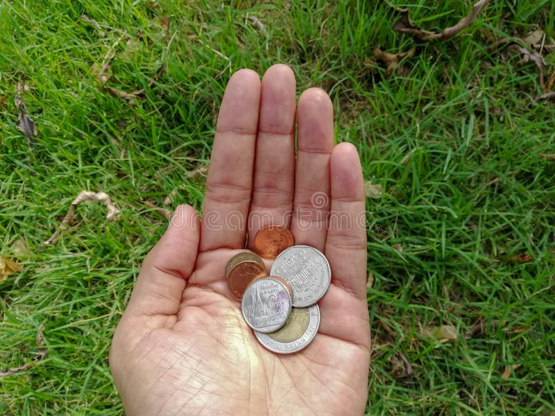 A hand holding the remain coins, five, ten, one, and zero point twenty-five Baht coins. Small money but valuable for poor people stock photo