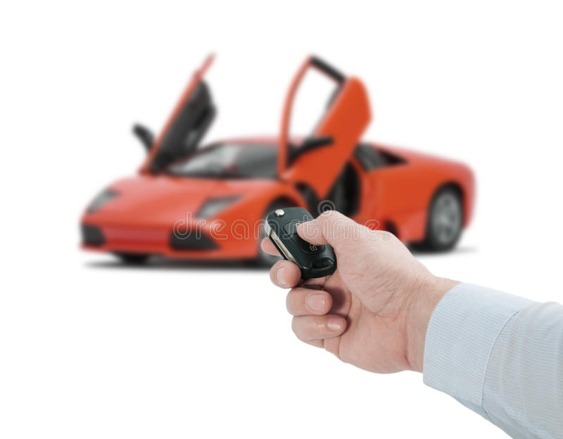 Hand holding a remote control key. Man hand holding a remote control key near the red sports car with open doors on a white background royalty free stock photography