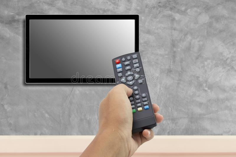 Hand holding remote control at television screen royalty free stock images