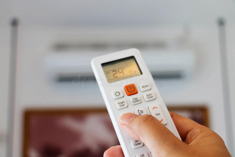Hand holding remote controller. To adjust temperature royalty free stock photos