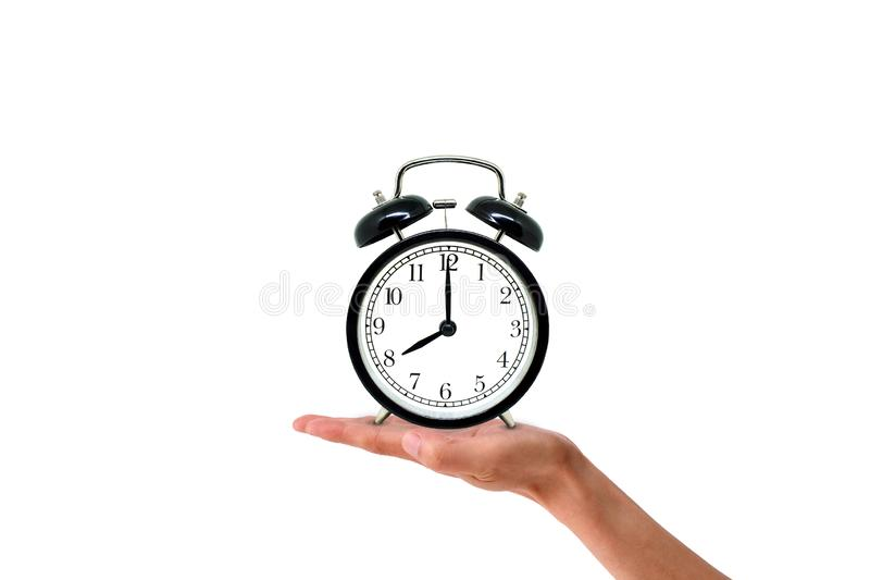 Hand holding retro black alarm clock that showing eight o`clock isolated on white background. royalty free stock images