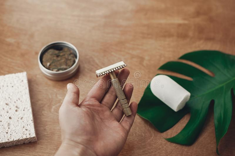 Hand holding reusable vintage razor for shaving on background of natural soap, solid shampoo bar, eco deodorant, sponge on wood. With green monstera leaf. Zero stock photo