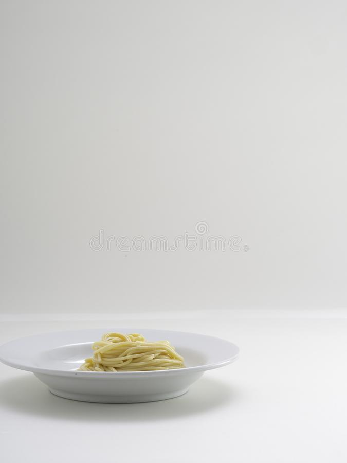 Hand holding roll pasta spaghetti with a fork and bish. On white background royalty free stock image