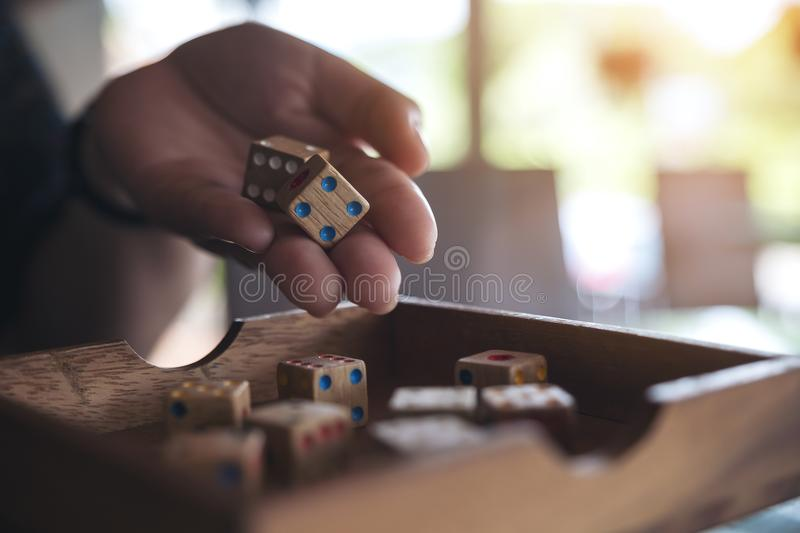 Hand holding and rolling wooden dices royalty free stock image