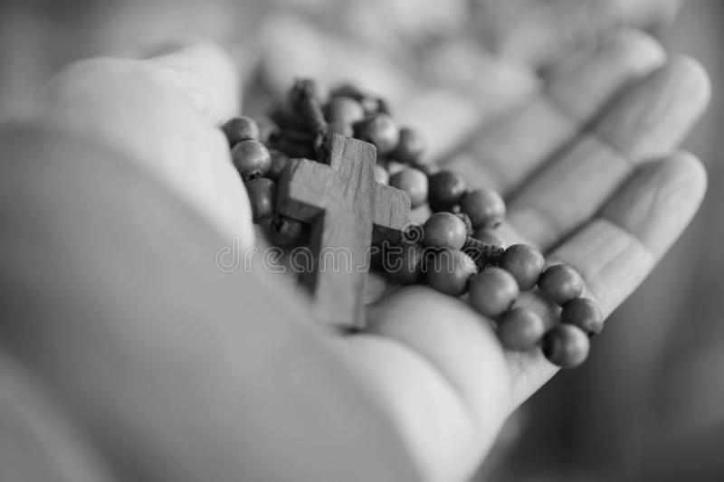 Hand holding Rosary in black and white background. Senior woman holding rosary with open hand with Jesus Christ Cross Crucifix. stock image