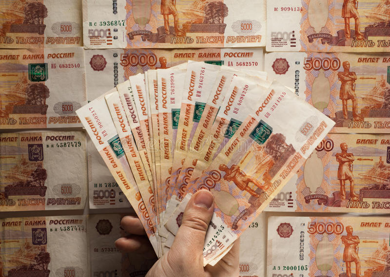 Hand holding Russian banknote, on russian money background. royalty free stock image