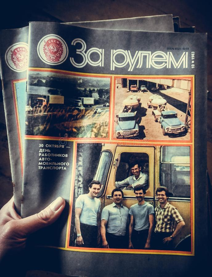 Hand holding a Russian magazine behind the wheel royalty free stock image