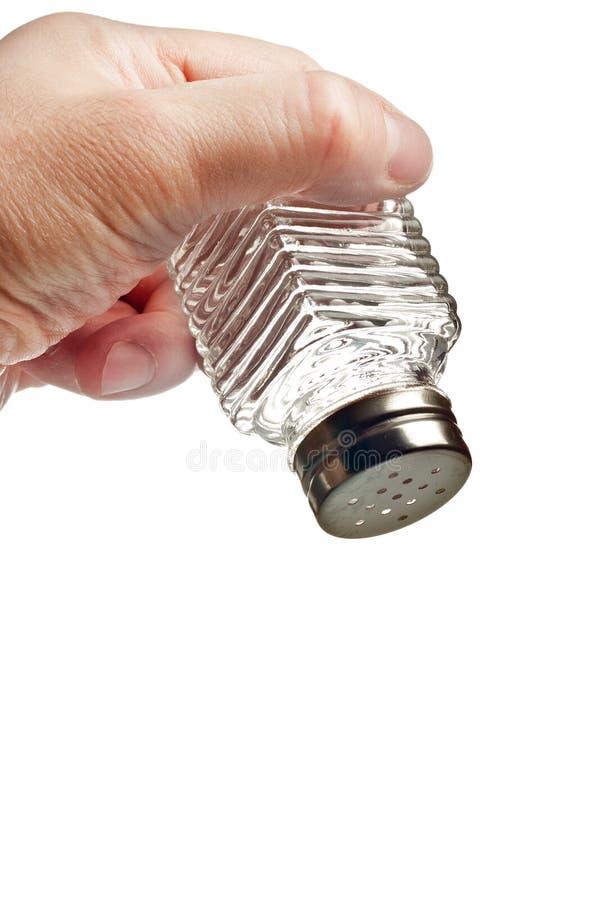 Hand holding salt shaker. Isolated over white stock photo