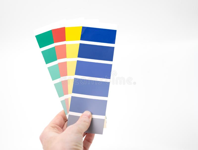 Hand holding selection of colour swatches stock photography