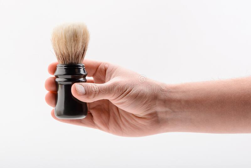 Hand holding a shaving brush on white background royalty free stock images