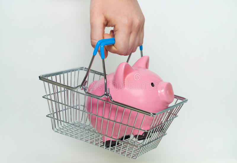 Hand holding shopping basket with piggy bank. On white background royalty free stock image