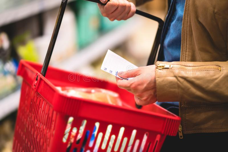 Hand holding shopping list and basket in grocery store aisle. Woman reading paper, shelf in the background. Lady buying groceries in supermarket. Consumer in royalty free stock photo