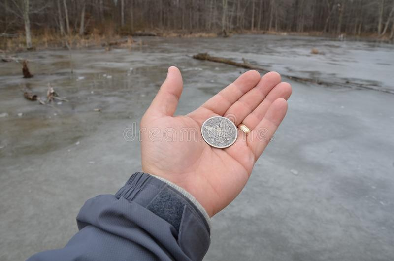 Hand holding silver coin in wetland area with frozen water royalty free stock images