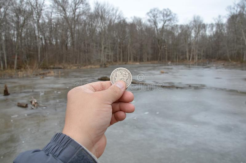 Hand holding silver coin in wetland area with frozen water. Hand holding silver coin or money in wetland area with frozen water and trees stock photography