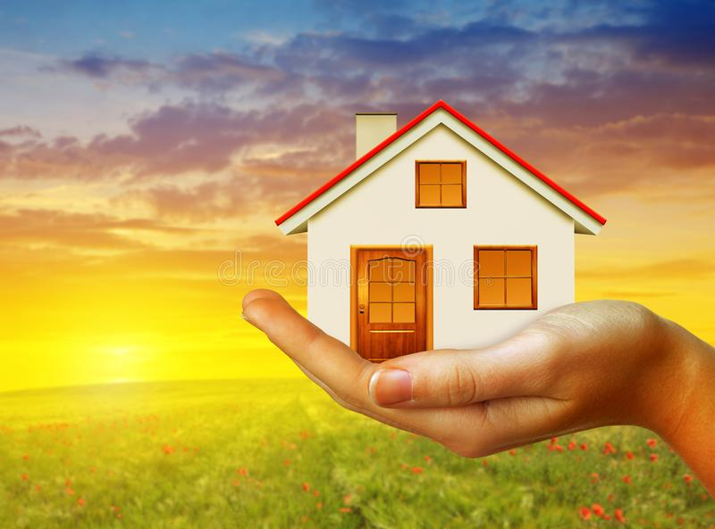Hand holding small house at sunset. stock photo