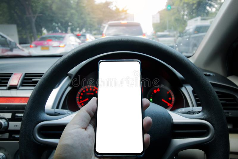 Hand holding smart phone with blank screen. On the car stock photo