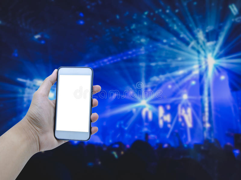 Hand holding smart phone on blurred concert royalty free stock photo