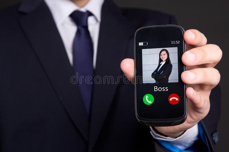 Hand holding smart phone with incoming boss call. Male hand holding smart phone with incoming boss call stock image