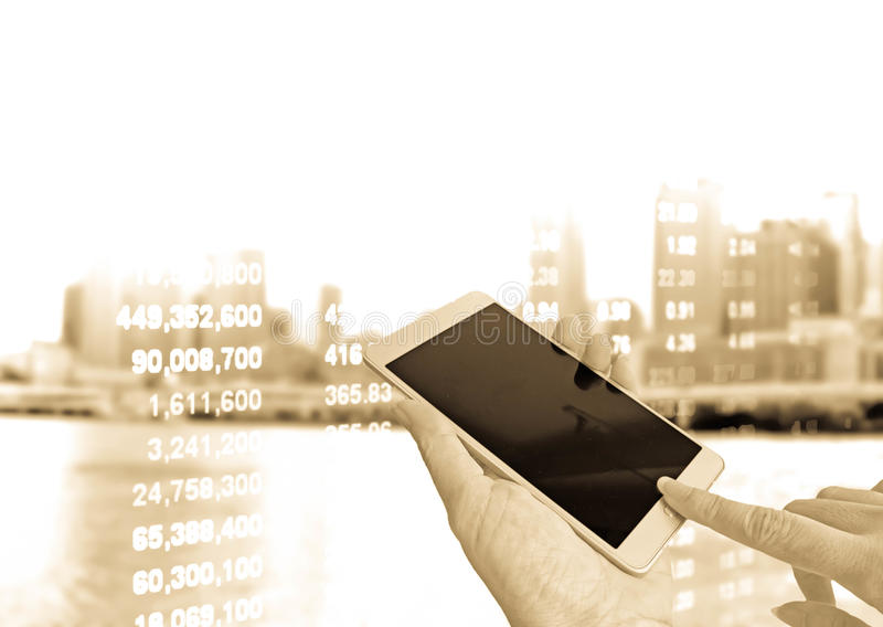 Hand holding smart phone on stock price. And blurred building background in vintage filter stock photography