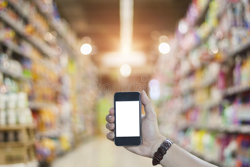 Hand holding smart phone in super market. Hand holding blank screen smart phone in super market, vintage light royalty free stock images