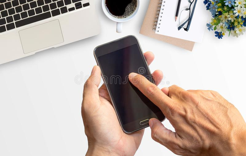 Hand holding smart phone with white minimal office desk table stock image