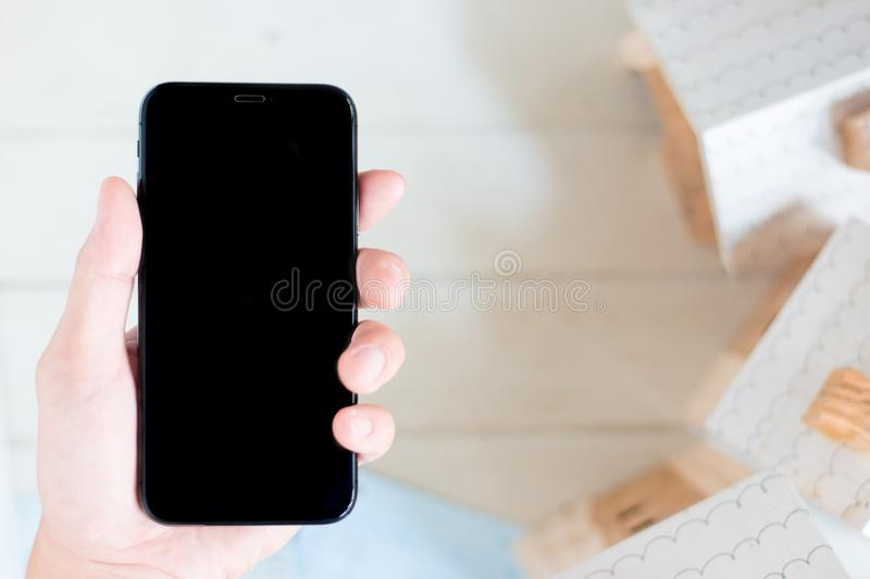 Hand holding smartphone with account book and Miniature house model. On white wood background royalty free stock images