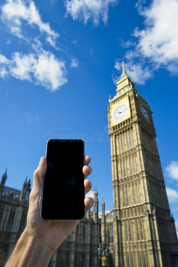 Hand Holding Smartphone at Big Ben Westminster Palace London. Hand holding blank screen smartphone outside Big Ben Westminster Palace London under bright blue royalty free stock photos