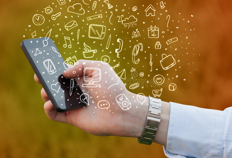 Hand holding smartphone with hand drawn media icons and symbols. Concept stock photos