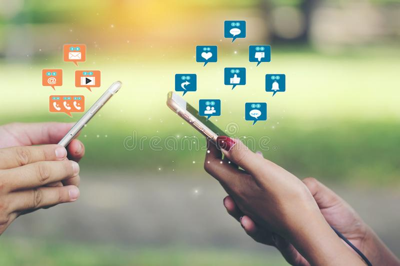 Hand holding smartphone with hologram or icon of set of social media on green background, Communication technology and Social royalty free stock image