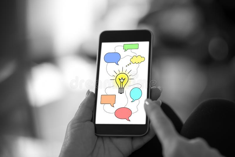 Idea concept on a smartphone. Hand holding a smartphone with idea concept stock photo