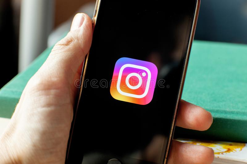 Hand holding a smartphone with an Instagram icon on screen. royalty free stock photos