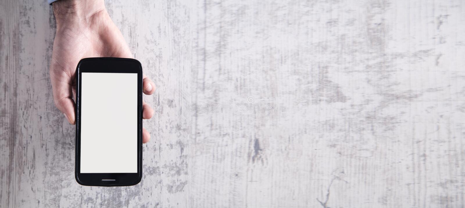 Hand holding smartphone in modern white desk royalty free stock photos