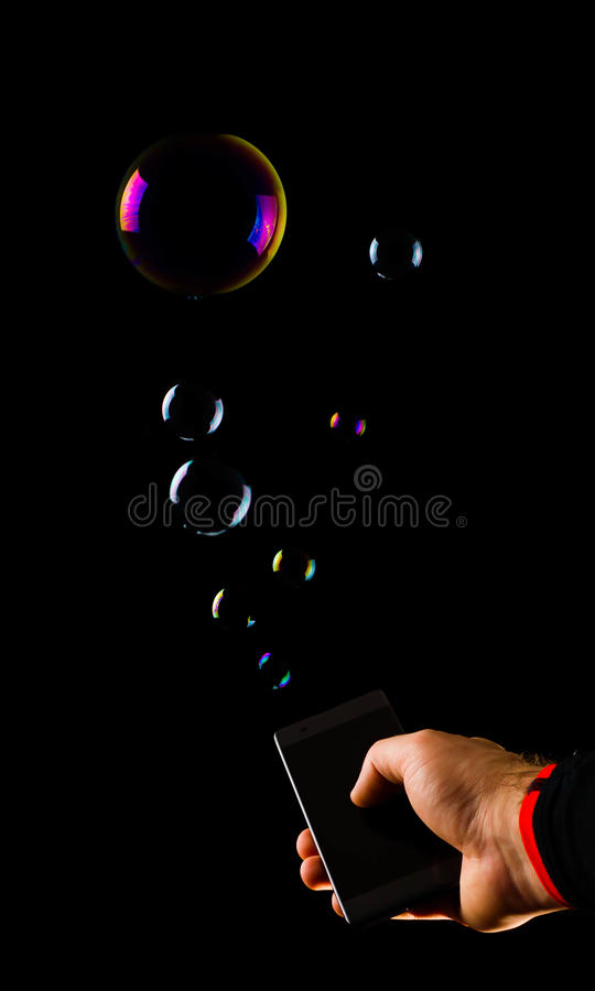 Hand holding smartphone sms mms bubbles gadget action. Hand holding smartphone with hand drawn media icons and symbols concept sms mms bubbles gadget action stock photos