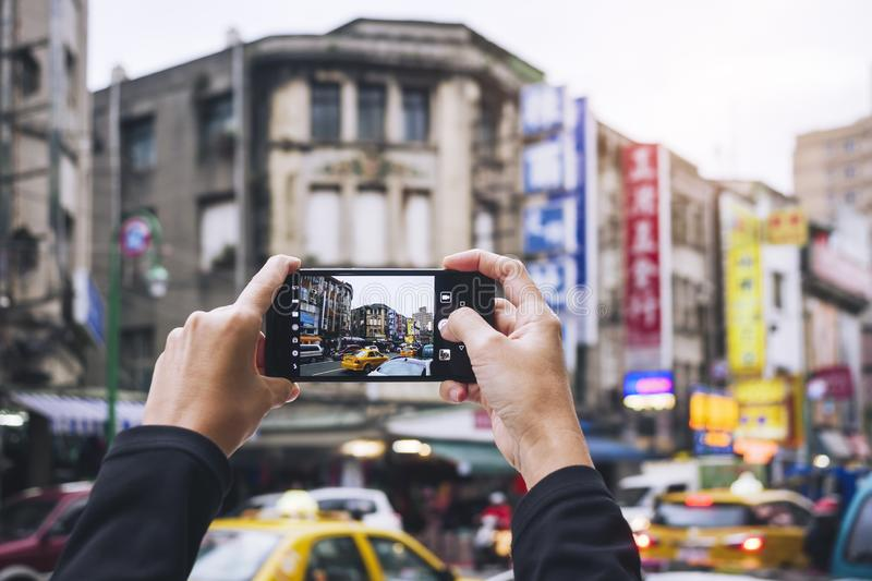 Hand holding Smartphone Take photo Old building city street Taipei tourist spot. Social media share royalty free stock images