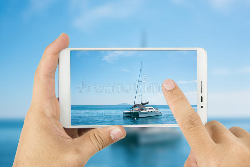 Hand holding a smartphone to take pictures of sailing. In. Man hand holding a smartphone to take pictures of sailing. In the quiet sea stock photography