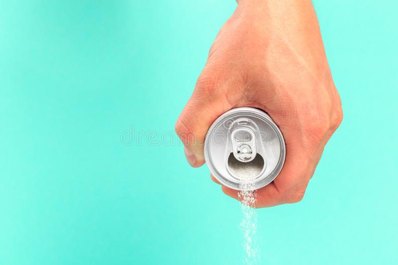 Hand holding soda can pouring a crazy amount of sugar in metaphor of sugar content of a refresh drink isolated on blue background. In healthy nutrition, diet stock photography