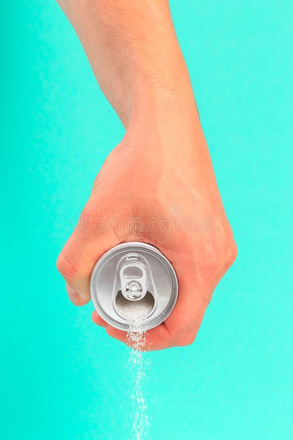 Hand holding soda can pouring a crazy amount of sugar in metaphor of sugar content of a refresh drink isolated on blue background. In healthy nutrition, diet stock photos