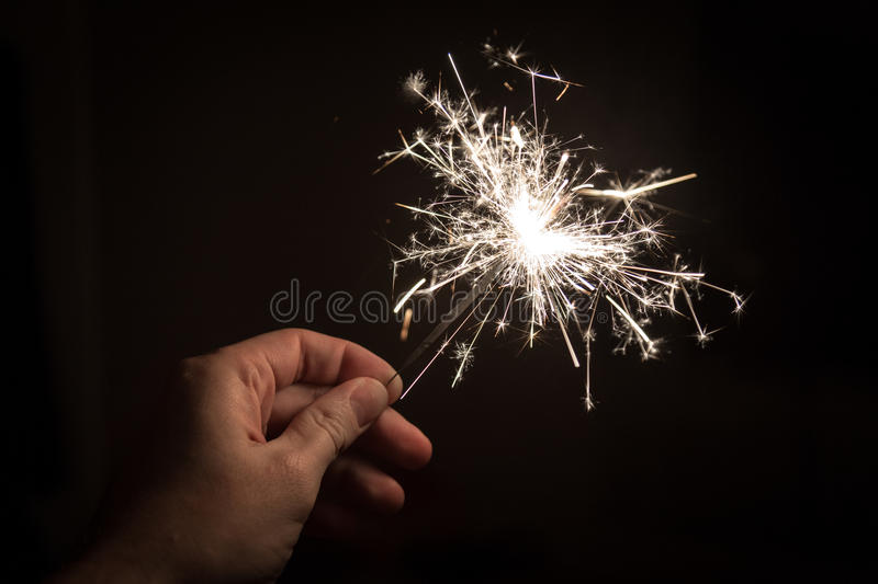 Hand holding sparkler. A hand holding a sparkler on a black backgournd royalty free stock photography