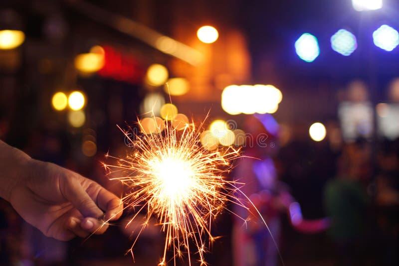 Hand holding sparkler or firework on street night background. Man hand holding sparkler or firework on street night background royalty free stock photo