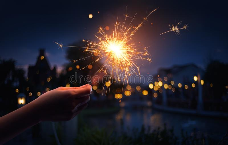 Hand holding a sparkler. With neighborhood background stock photo