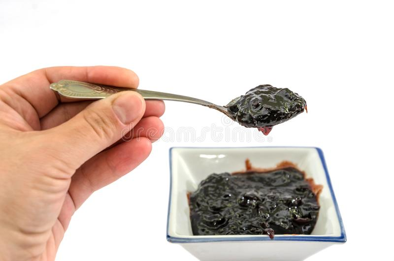Hand holding a spoon with jam on a white background royalty free stock images