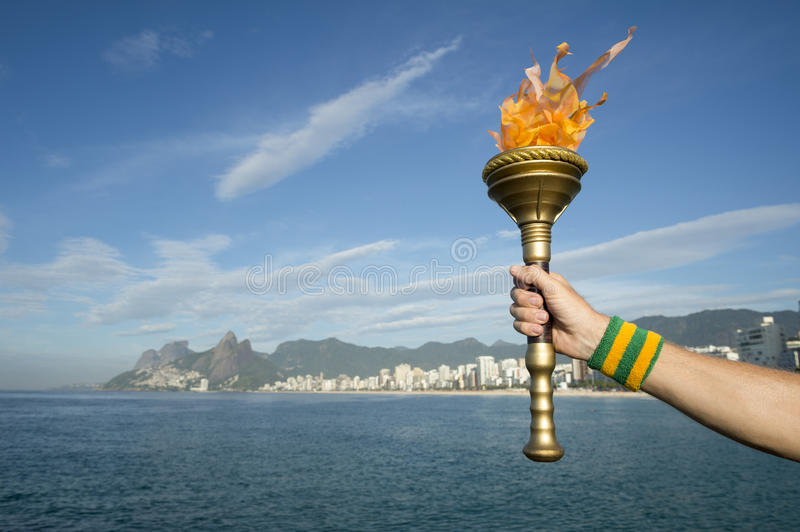Hand Holding Sport Torch Rio de Janeiro. Hand of an athlete wearing Brazil colors sweatband holding sport torch against Rio de Janeiro Brazil skyline with Two stock images