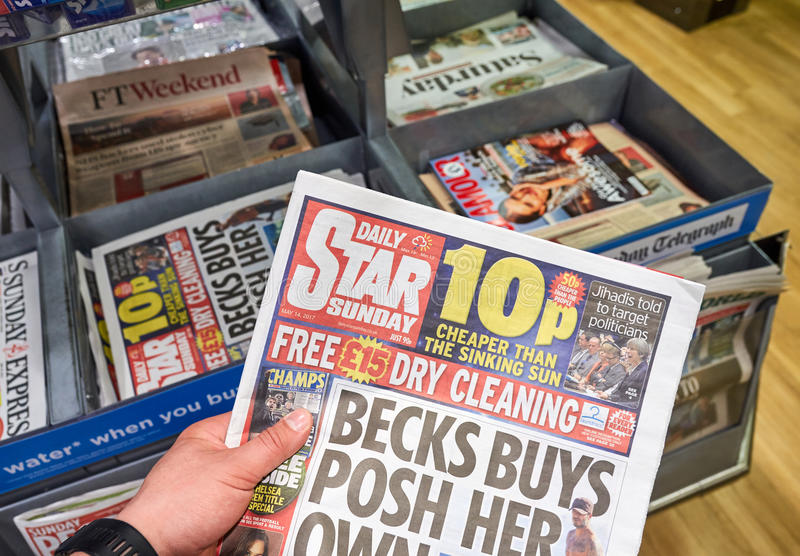 A hand holding Daily Star Sunday newspaper. LONDON, ENGLAND - MAY 14, 2017 : A hand holding Daily Star Sunday newspaper. The Daily Star Sunday is a weekly royalty free stock photos