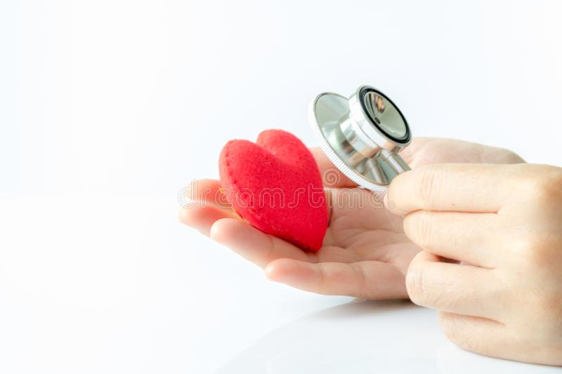 Hand holding stethoscope use to hear sounds within the red heart stock photo