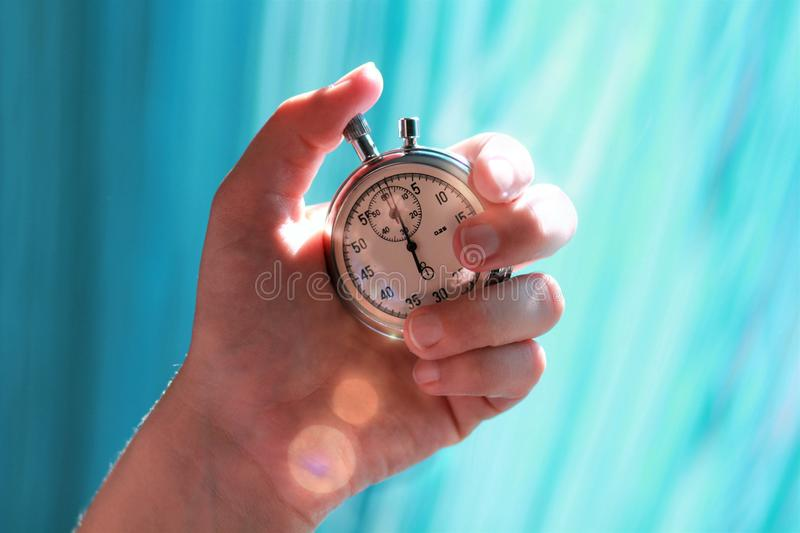 Hand holding a stopwatch and pressing the button to note the time. Sun rays flare stock image