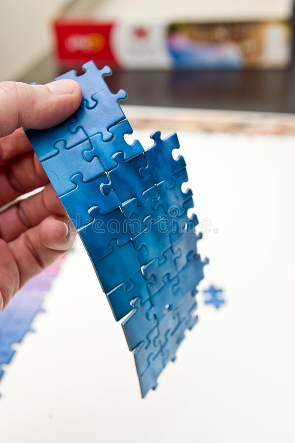 Hand holding a stripe of blue puzzle pieces stock photo