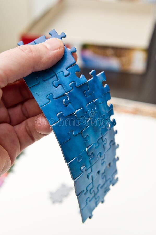 Hand holding a stripe of blue puzzle pieces royalty free stock images