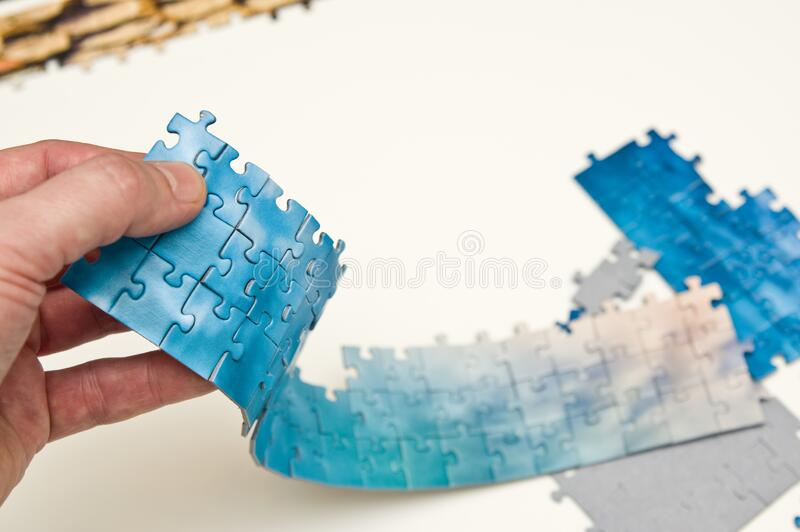 Hand holding a stripe of blue puzzle pieces stock images
