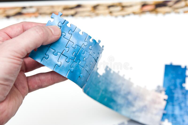 Hand holding a stripe of blue puzzle pieces stock photography